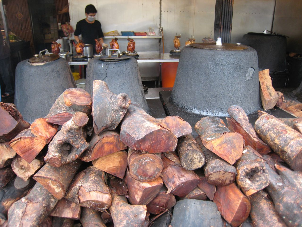 pile of wood in front of 3 kilns for roasting chicken